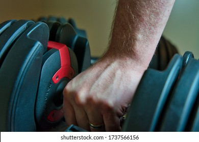 Hand gripping adjustable dumbbells for working out at home. male hand with ring visible.