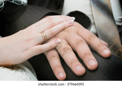 Hand of the groom to the bride's hand with wedding rings