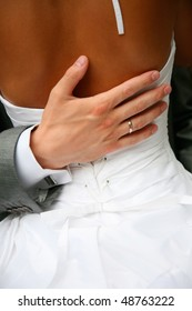 The hand of the groom gently embraces the bride's waist
