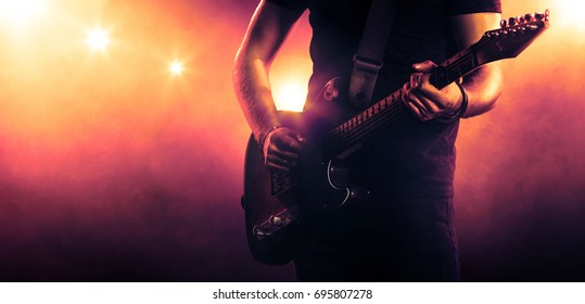 Hand of a guitar player holding a guitar