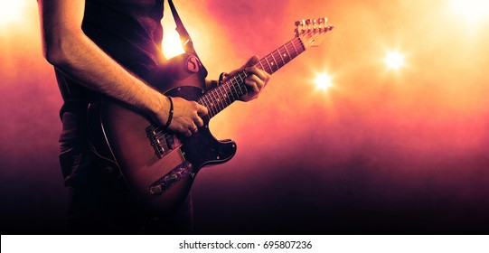 Hand of guitarist playing a guitar