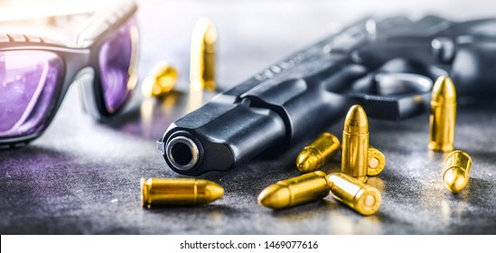 Hand gun with ammunition banner or panorama, on dark stone background with tactical glasses. 9 mm pistol gun military weapon and pile of bullets at the metal table.