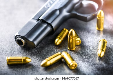 Hand gun with ammunition on dark stone background. 9 mm pistol gun military weapon and pile of bullets at the metal table.
