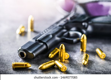 Hand gun with ammunition on dark stone background with tactical glasses. 9 mm pistol gun military weapon and pile of bullets at the metal table.