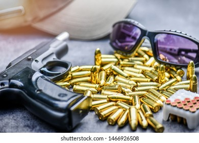 Hand gun with ammunition, tactic glasses on stone background. 9 mm pistol gun weapon and bullets round pile at the stone table .