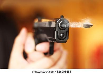 hand gun fire flying bullet