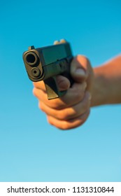 Hand gun firearm aimed in violent pose pointing at viewer