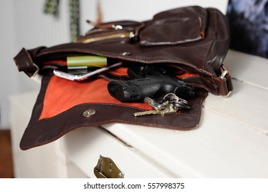 Hand gun inside a lady handbag for safety and protection and self-defense