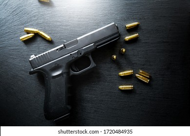 Hand gun on black background, bullets and handcuffs. 9mm pistol with ammunition on dark table.