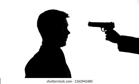 Hand with gun pointing male head, life threat, illegal money extortion, robbery