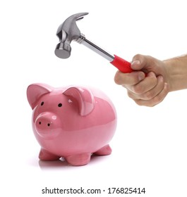 Hand with hammer about to smash piggy bank to get at savings