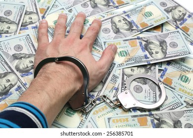 Hand in handcuffs on a pack of dollars