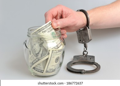 Hand in handcuffs is taking dollars from  glass jar on gray background