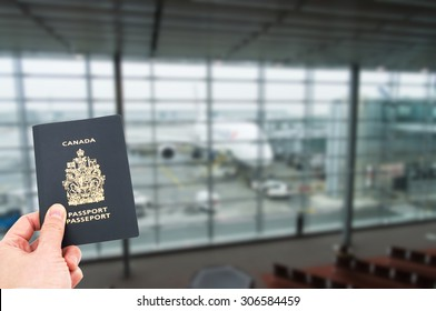 Hand handing Canadian passport with airplane in background, boarding concept