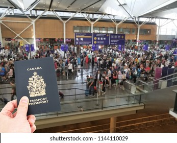 Hand handing Canadian passport at airport custom counters, immigration concept