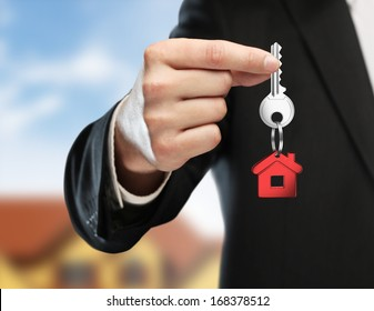 hand handing key on cottage background