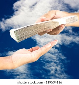 Hand handing over money to another hand on blue sky  background