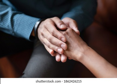 Hand in hands. Close up of young man husband boyfriend holding hand of beloved mixed race woman wife girlfriend comforting supporting in grief, asking forgiveness, apologizing after family argument