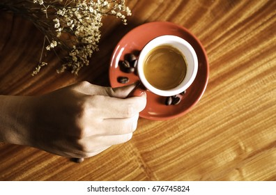 Hand hanging a cup of coffee