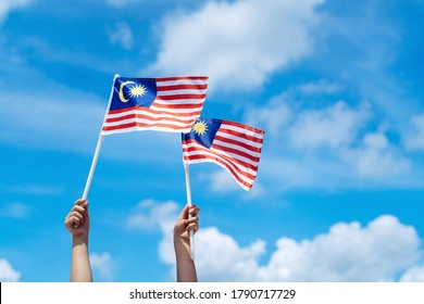 Hand happily waving Malaysia flag against blue sky. Celebrate Independence Day & Merdeka day.