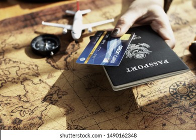 Hand has passport and credit card, has world map, travel concept