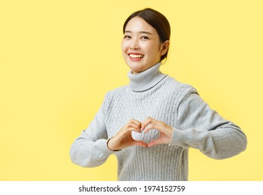Hand heart gesture from Asian woman, Cute female showing hand heart gesture over chest and at camera, making love confession standing at yellow background and copy space.
