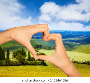 Hand in heart gesture over Tuscany landscape
