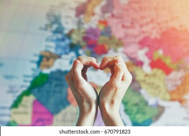 hand in heart shape with love on world map background