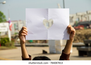 Hand held heart shaped paper holds up and there is a train station view on the back of the paper.