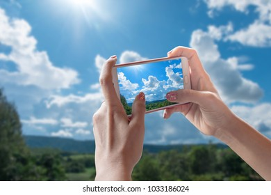 Hand held mobile phone on sky background Technology