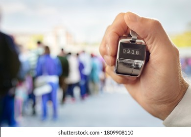 Hand held tally counter counting headcount of people in a queue