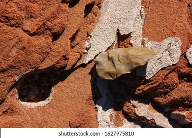 Hand hewn stone edge (mesolithic) silex tool lying on reddish sand stone