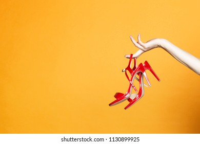 Hand with high heels shoe on yellow background