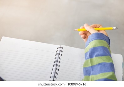 hand high school or university student in uniform holding pencil writing on paper answer sheet.sitting on lecture chair taking final exam or study attending in examination room or classroom