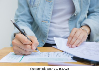 hand high school or university student in casual holding pencil writing on paper answer sheet.sitting on lecture chair taking final exam or study attending in examination room or classroom