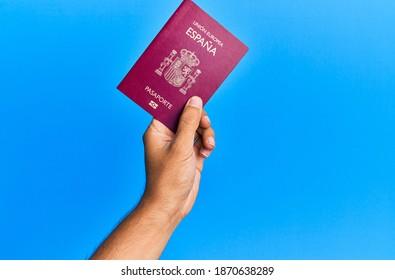 Hand of hispanic man holding spanish passport over isolated blue background.