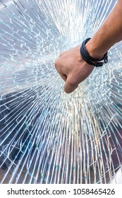Hand hitting the glass and smashing the glass all shattered
