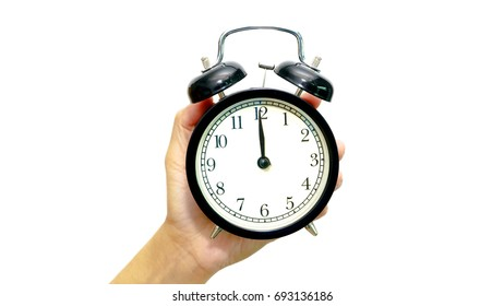 Hand hold an alarm clock with showing 12 o'clock. White background. Time concept.