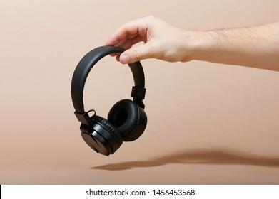 Hand hold black headphones on beige color background