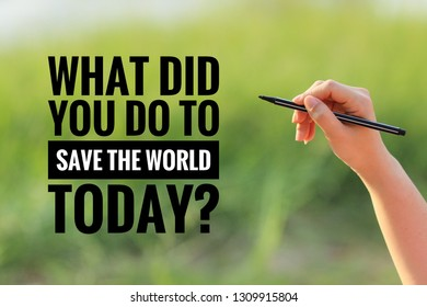 """a hand hold a black pen writing word """"what did you do to save the world today?"""" on the green field background - save the world concept"""