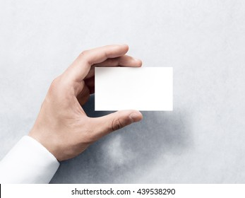 Hand hold blank plain white business card design mockup. Clear calling cards mock up template holding arm. Visit pasteboard paper surface display front. Check small offset print. Business branding