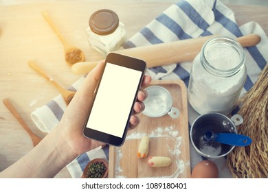 hand hold blank screen cellphone, smartphone, tablet on top kitchen table with cookware, concept of healthy care life style.