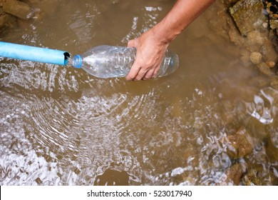 hand hold bottle - fill a bottle with water from natural stream in forest of camping