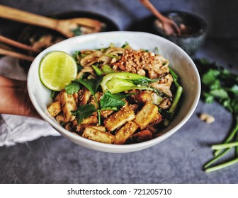 Hand hold bowl Udon with Padthai sauce, Healthy Vegetarian/vegan menu; Padthai noodle with smoke tofu and mixed vegetable - chinese baby Bok Choy , garlic chive, shallot and crushed peanut topping.