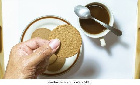 Hand hold brown biscuits in dish pairing with black coffees with teaspoon