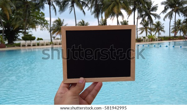 hand hold chalkboard at the pool. Composition of Nature.