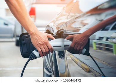 Hand hold of charging modern electric car battery on the street which are the future of the Automobile, Close up of power supply plugged into an electric car being charged for hybrid