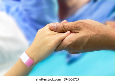 hand hold a child's patients hand with bracelet