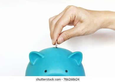 Hand hold a coin deposit in big blue piggy bank. show concept and ideal of investment, retirement, saving, wealth and growth.
