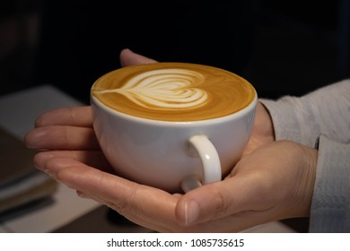The hand hold a cup of capuchino coffee with heart shape of milk cream on top.